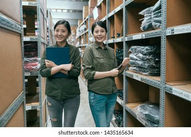 Distribution warehouse manager and colleague look to camera smiling. two beautiful women employee working in stockroom standing with crossed arms confidently. young girls team partners in storehouse.
