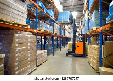 Distribution warehouse worker moving boxes on pallet with forklift
