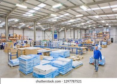 Distribution warehouse worker pulling boxes on pallet truck