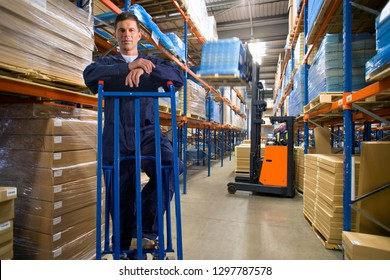 Distribution warehouse worker with trolley looking at camera