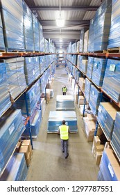 Distribution warehouse workers pushing pallet trucks with boxes