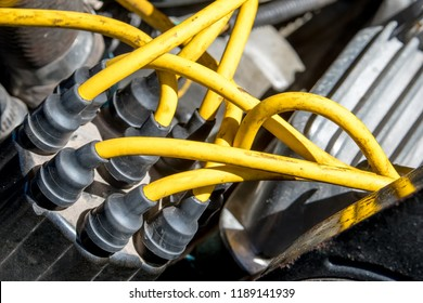 Distributor cap and high performance yellow ignition wires on a car engine.