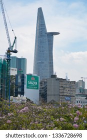 DISTRICT 1, SAIGON DOWNTOWN, HO CHI MINH CITY, VIETNAM - APRIL 2018: Symbol of dynamic modern city and Tabebuia rosea flowers