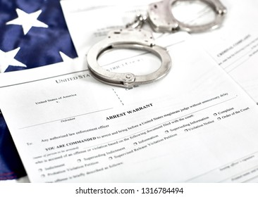 District Court Arrest Warrant court papers with handcuffs on the American flag isolated on white with shallow depth of field