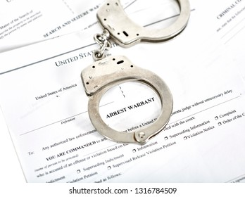 District Court Arrest Warrant court papers with handcuffs isolated on white with shallow depth of field
