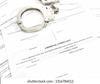District Court criminal complaint, arrest warrant and search and seizure warrant doccuments with handcuffs isolated on white