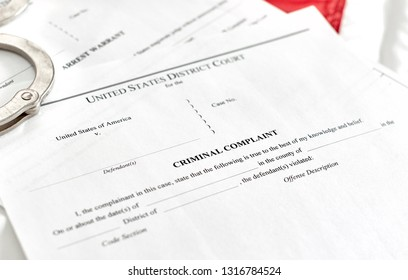 District Court criminal complaint, arrest warrant and search and seizure warrant doccuments on the American flag with handcuffs isolated on white