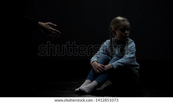 Distrustful little girl sitting in dark room refusing adult helping hand, fear