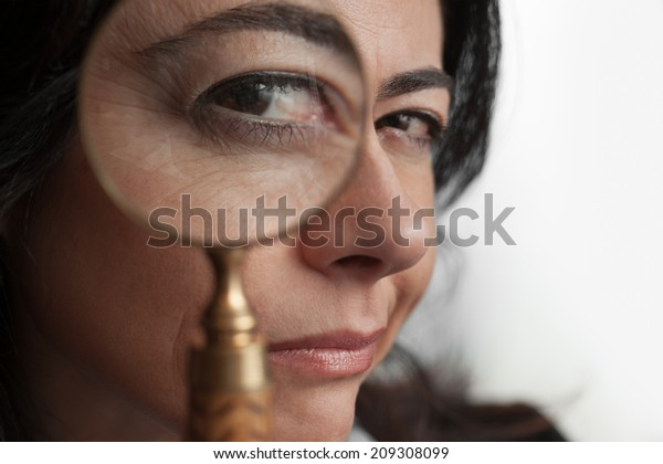 Distrustful woman looking through a magnifying glass.
