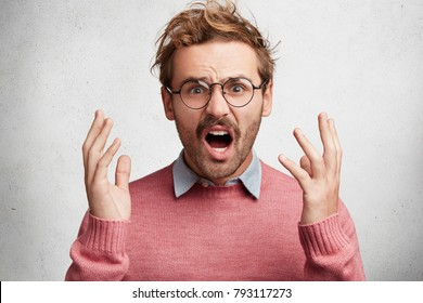 Disturbed displeased man gestures angrily, has irritated expression, can`t recieve critic on his side, exclaims in despair. Young male has quarrel with someone, tries to prove his rightness.