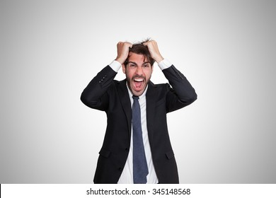 Disturbed young business man going wild by pulling his hair, on gray background.