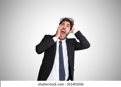Disturbed young business man scared by something, on gray background.