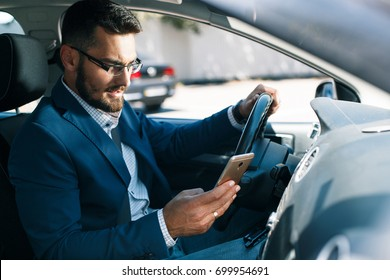 Disturbed young businessman with phone in his hand seating in car