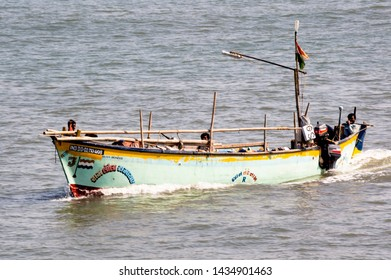 Diu, Daman, Gujarat, India - Circa 2019: Colorful open boat sailing in the blue sea of daman diu. The blue green hull and the open boat with its mast and outboard motor show a tourist or a fishing