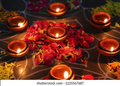 diva with   rangoli. diva isolated with black background. diva with hand in rangoli background