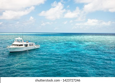 Dive boat on the great barrier reef in Cairns, Queensland, Australia. Crystal clear blue water, similar to florida and Bahamas coastline.
