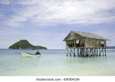 Dive Boat and Water Hut, with View of Kri Island and Dampier Strait. Raja Ampat, Indonesia