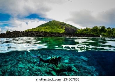 Diver below the surface in Banda, Indonesia underwater photo. There are various coral reefs.