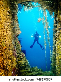 Diver with camera and lights  approaching WWII wreck at Truk Lagoon, Micronesia.