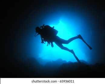Diver at a cave facing bluewater in the background