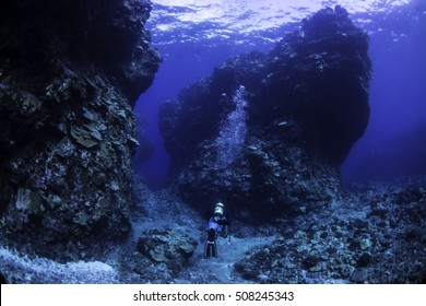 A diver choosing one channel between lava formation and the other