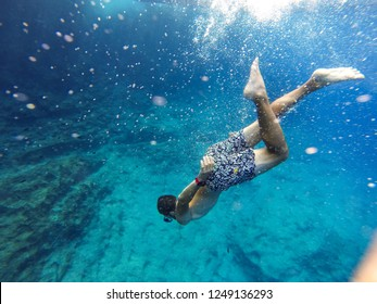 diver dives underwater, diver swims down to the bottom, snorkeling