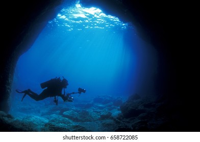 Diver at the enterance of a marine cave, Sarigerme Turkey.