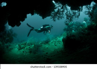 A diver explores the mouth of a deep cave in Raja Ampat, Indonesia.  This area is known for its high marine diversity and great scuba diving.