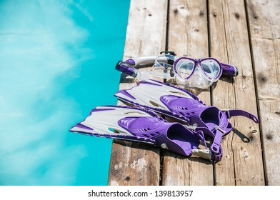 Diver eyeglasses, diving goggles, scuba snorkel and fins or flippers on the jetty (wood deck) near the water