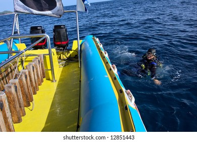 Diver floats in water next to white-blue boat. Shot in Sodwana Bay, KwaZulu-Natal province, Southern Mozambique area, South Africa.
