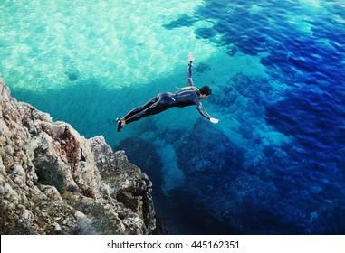 A diver jumps off a cliff