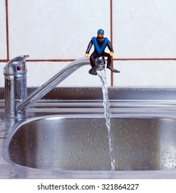 diver made of plasticine sitting on tap kitchen faucet