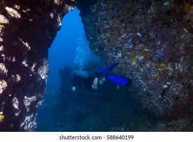 Diver passing through tunnel underwater of Samui