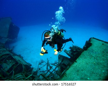 Diver photographing a Sunken Shipwreck in Cayman Brac