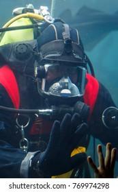 Diver saying goodbye to a kid in aquarium