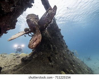Diver at a ship wreck in the Caribbean Sea around Curacao with ship's propeller in foreground