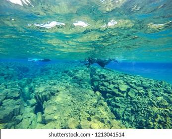 Diver at Silfra fissure, Þingvellir, where the European and American Plates meet. Thingvellir National Park near Reykjavik, Iceland