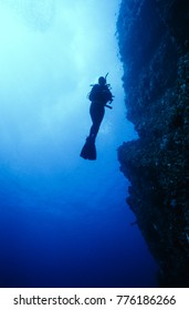 A diver silhouetted against the light on a vertical wall reef in Indonesia