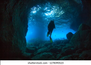 Diver swimming through a sea cave near Poor Knights Islands, North Island, New Zealand.
