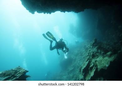 diver undersea pass through cave