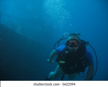 A diver with a wreck in the background