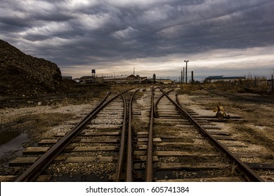 Diverging railroad tracks meet at an abandoned foundry on a moody, overcast evening in Columbus, Ohio.