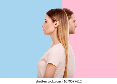 Diverging views. Pleasant young woman and her boyfriend standing in a line but looking into different directions while posing against blue and pink backgrounds respectively