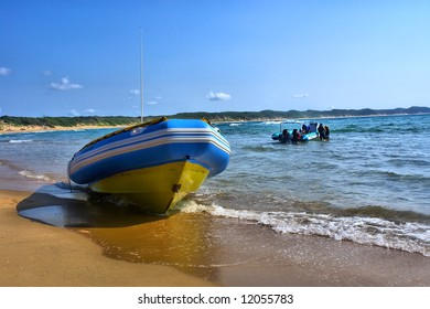 Diver's boat lies on beach, another one goes to trip. Shot in Sodwana Bay Nature Reserve, KwaZulu-Natal province, Southern Mozambique area, South Africa.