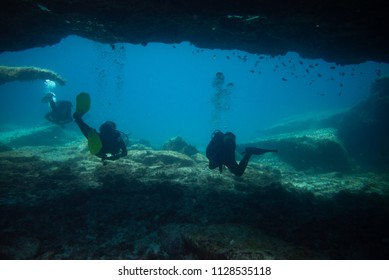 divers comes out of an underwater cave, fuerteventura canary islands