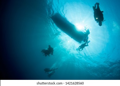 Divers descend in clear, blue depths of Komodo National Park, Indonesia. This tropical area is part of the Coral Triangle and is a popular destination for divers and snorkelers.