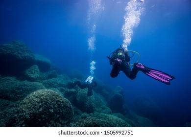 Divers enjoying underwater world beauty. Mediterranean sea near Hvar Island, Croatia.
