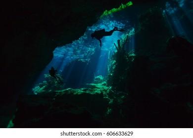 Divers exploring hidden reefs in underwater cave