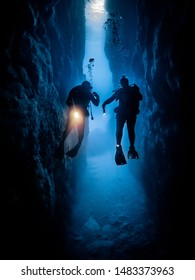 divers exploring through a tunnel