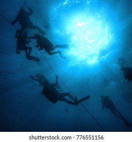 divers holding rope at the end of a dive with the sun light  on top of the watter